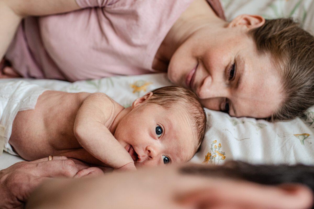 Mutter liegt lächelnd neben Baby bei einem Familienshooting. Neugeborenen Fotografie in Celle