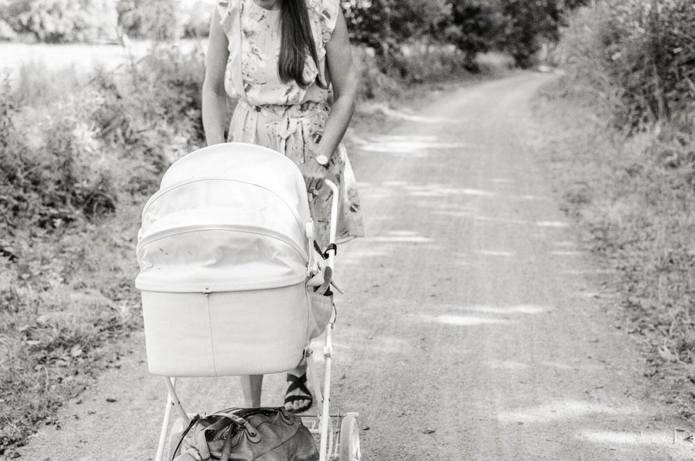 Mutter schiebt den Kinderwagen an den Dammaschwiesen in Celle Familienfotografie in Celle Outdoorshooting