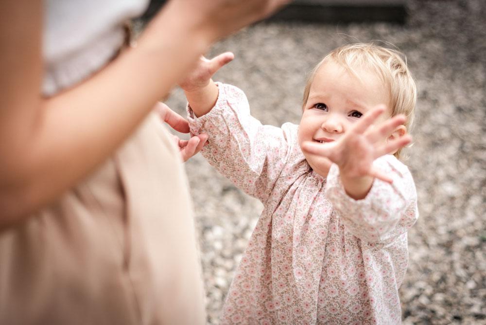 Mädchen streckt die Arme, um etwas zu bekommen. Dieses Foto entstand bei einer Einschulungsfeier im angelehnt an ein Familienshooting in Celle.