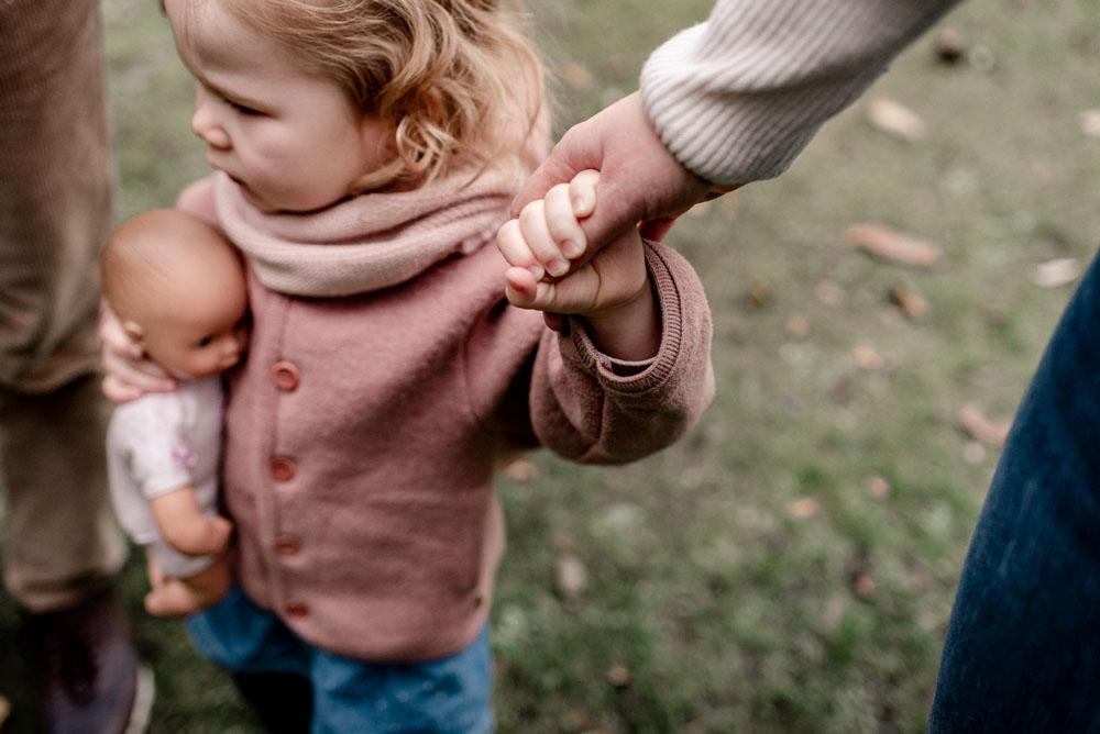 Kleines Mädchenhält Hand der Mutter bei einem Familienshooting in Celle. Detailaufnahme Familienfotograf Celle