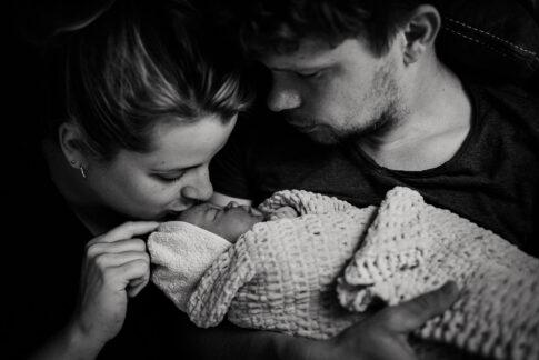 Mutter und Vater betrachten und küssen ihr Neugeborenes nach Hausgeburt, dokumentiert von Geburtsfotografin Lisa von Rekowski
