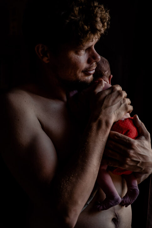 Vater mit Neugeborenen auf Arm nach Hausgeburt , dokumentiert von Der Geburtsfotografin Lisa von Rekows