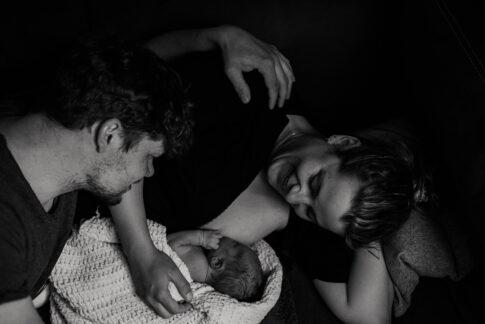 Die frischgebackenen eltern betrachten ihr Baby bei Geburtsshooting in Ilsenburg