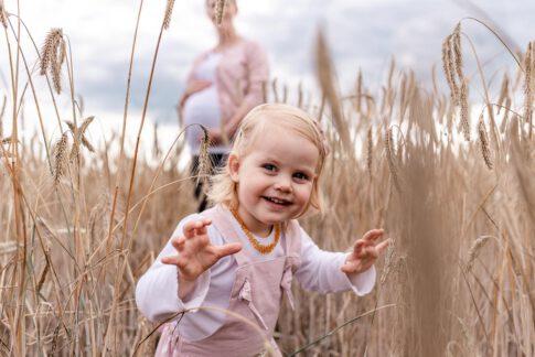 Dier zukünftige große Schwester schaut beim Babybauchshooting durch ein Kornfeld Celle. Im Hintergrund sieht man die Mama mit ihrem schönen Babybauch.