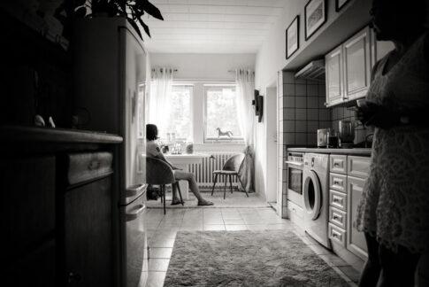 Frau sitzt in Küche , gedankenverloren. Eine andere Frau steht an Küchenzeile gelehnt. Das Gesicht kann man nicht erkennen.