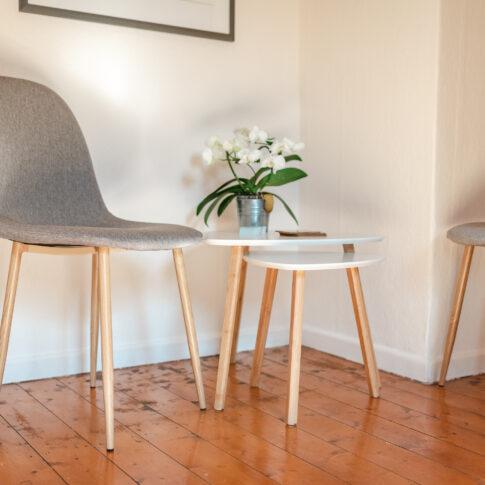 Ein helles und freundliches Wartezimmer. Mit Holzfußboden und zwei Stühlen und einem kleinen weißen Tischchen. Auf dem Tisch liegen Visitenkarten von Anke Behrens aus Celle.