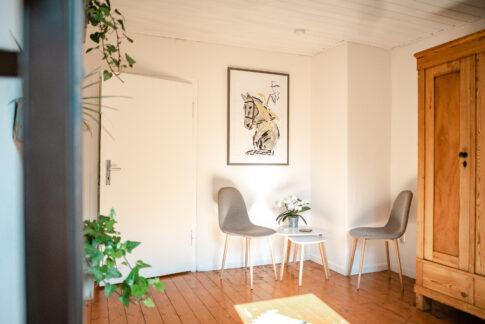 Warmer und freundlich gestalteter Coachingraum von Anke Behrens aus Celle. Zwei Stühle und ein Tisch. stehen neben einem Holzschrank.