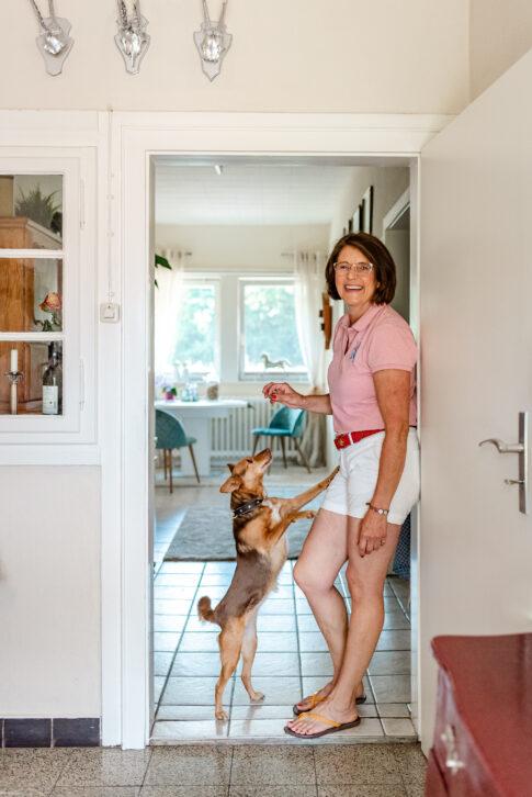 Anke Behrens steht im Türrahmen und hält ihrem Hund ein Leckerli entgegen. Dieser Hund springt an ihr hoch. Sie lächelt. Eine witzige Situation.