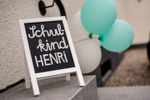 Ein Bild einer Einschulungsfeier. Es zeigt einen Aufsteller, der die Gäste auf den Anlass aufmerksam macht. Schulkind Henri steht darauf.