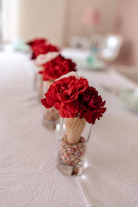 Rote Nelken in Waffeltüten als Tischdeko zur Einschulungsfeier.