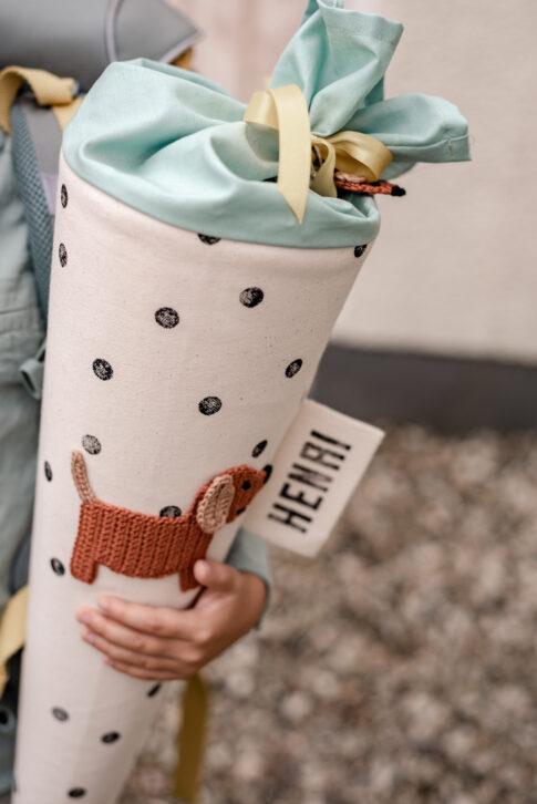 Eine Schultüte weiß mit schwarzen Punkten auf der ein braun gehäkelter Dackel appliziert wurde. Ein mintfarbener Stoff zum Zubinden mit gelber Schleife.