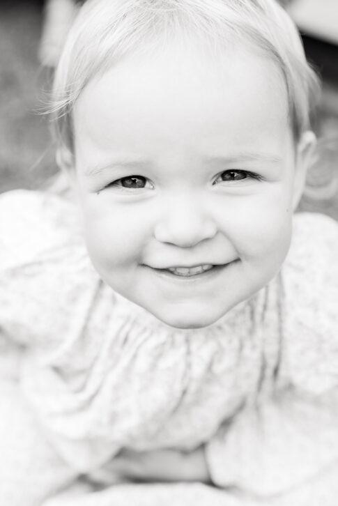 Ein strahlendes und verschmitztes Lächeln eines kleinen Mädchens in Porträtform in Schwarzweiß.