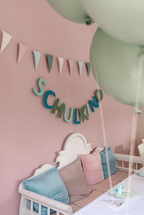 Eine festlich gedeckte und liebevoll dekorierte Tafel zur Einschulung. Im Hintergrund hängt eine Girlande welche das Wort Schulkind zeigt.