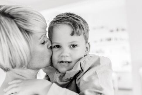 Die stolze Mutter gibt ihrem frischgebackenem Schulkind einen Kuss. Fotografie in schwarzweiß.