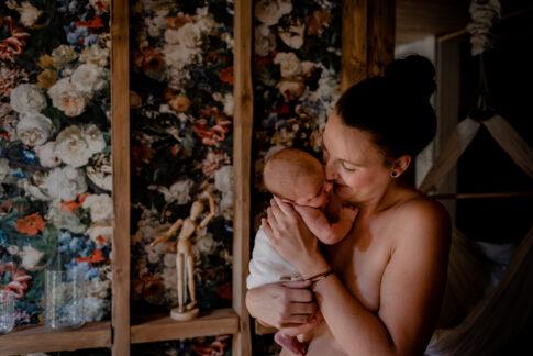 Nach dem Stillen kuschelt die Mama ihr Neugeborenes im Stehen an sich und gibt Ihm einen Nasenkuss.