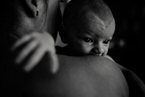 Fotografie eines Neugeborenen in schwarzweiß :mit wachen Augen blickt es über Mamas Schulter.