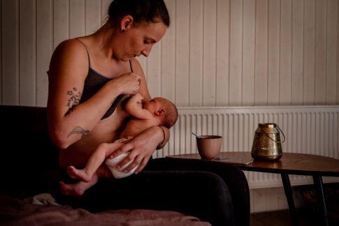 Wochenbettshooting. Die Mutter stillt ihr Neugeborenes auf dem Sofa. Neben ihr steht ihr kaltgewordener Kaffee.