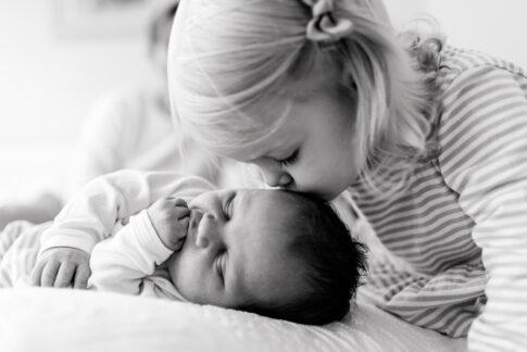 Schwarzweißfotografie beim Familienshooting in Hannover. Große Schwester küsst ihren neugeborenen Bruder.
