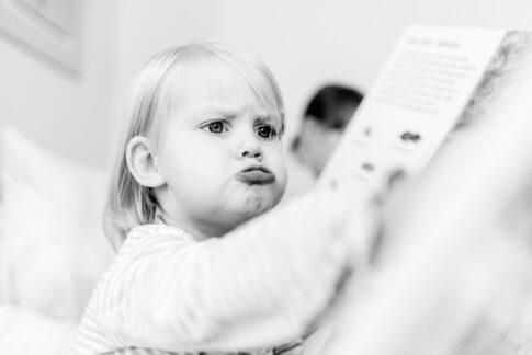 Bild eines Familienshootings in schwarzweiß von Lisa von Rekowski Fotografie. Mädchen schaut sich ein Buch an.