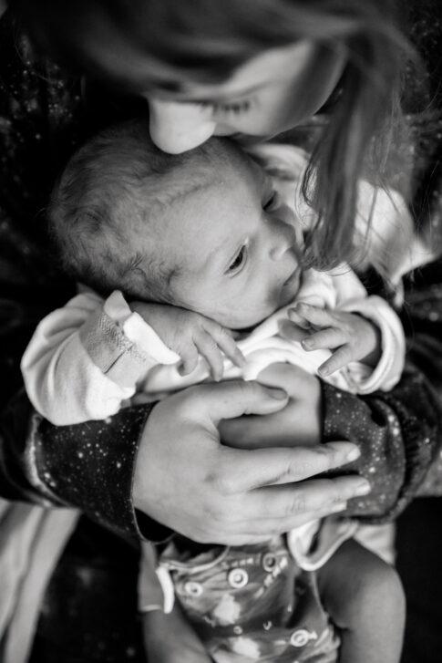 Neugeborenes auf Schoß der Schwester in schwarz weiß