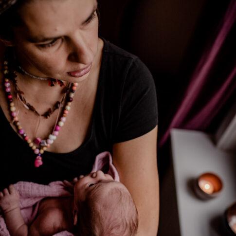 Mutter mit Neugeborenen auf Arm schaut aus dem Fenster in Geburtsräumen von Wiebke Niemann