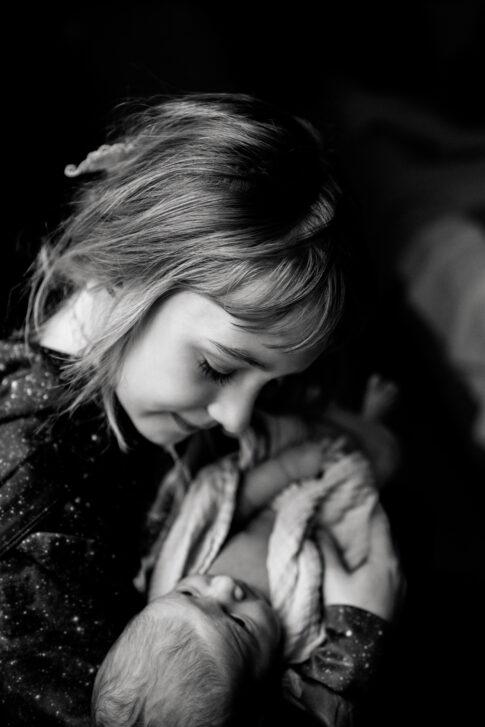 Neugeborenes auf Arm der Großen Schwester in schwarzweiß Geburtsräume Wiebke Niemann