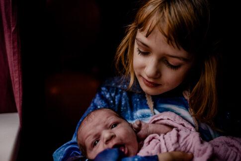 Große Schwester schaut verliebt auf Neugeborenes-Geburtsräume Wiebke Niemann