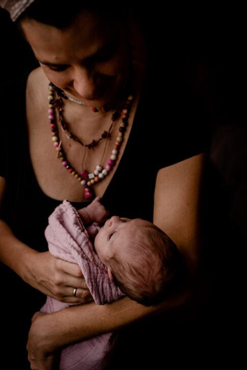 Neugeborenes auf Arm der Mutter- Wochenbettfotografie in Geburtsräumen von Wiebke Niemann