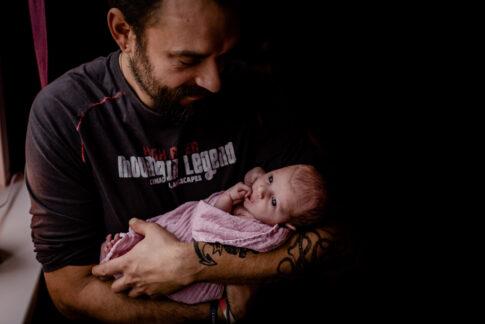 Neugeborenes Auf Arm des Vaters beim Wochenbettshooting in Geburtsräumen von Wiebke Niemann Doula