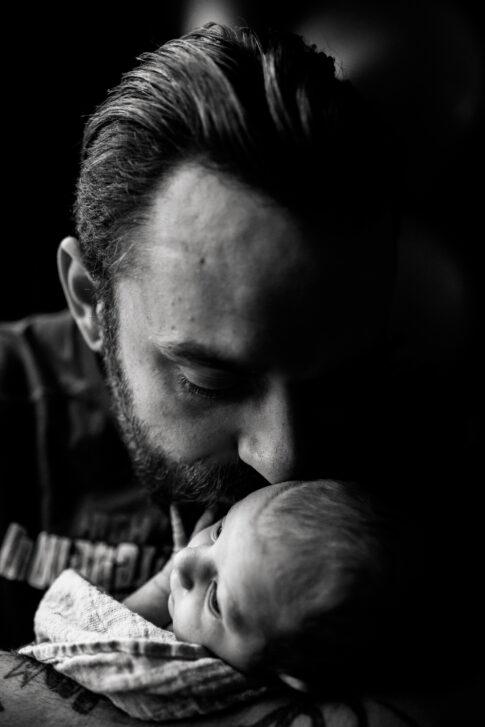 Vater küsst Neugeborenes in schwarzweiß beim Wochenbettshooting in Geburtsräumen von Wiebke Niemann Doula