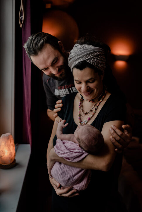 Vater und Mutter betrachten stolz ihr Neugeborenes beim Wochenbettshooting in Geburtsräumen von Wiebke Niemann Doula