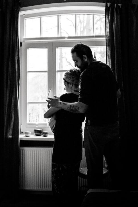 Vater und Mutter mit Neugeborenem in schwarzweiß Silhouette Wochenbettshooting in Geburtsräumen von Wiebke Niemann Doula