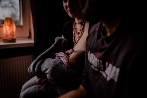 Mutter stillt ihr Neugeborenes Wochenbettshooting Geburtsräume in Kragen von Wiebke Niemann Doula