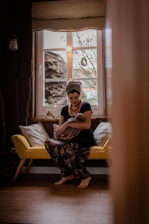 Mutter hält ihr Neugeborenes Wochenbettshooting Geburtsräume Wiebke Niemann Doula Lisa von Rekowski Fotografie
