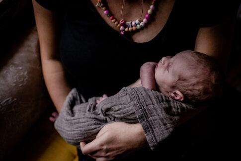Neugeborenes auf Arm der Mutter beim Wochenbettshooting in Geburtsräumen von Wiebke Niemann Doula Kragen von Lisa von Rekowski Fotografie