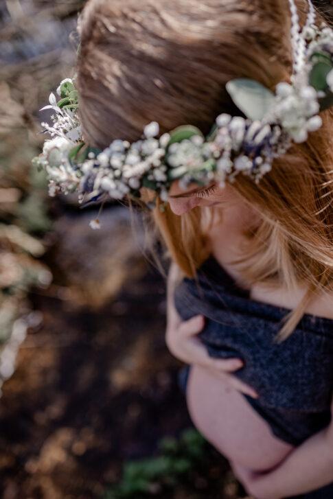werdende Mutter mit Blumenkranz im Haar beim Babybauchshooting in der Natur in Celle