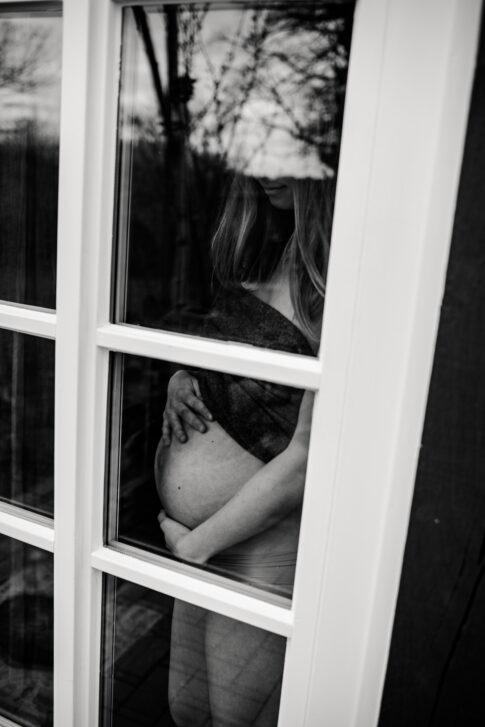 schwangere Frau steht am Fenster in schwarzweiß