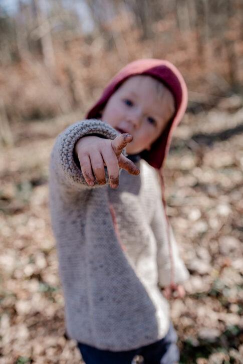 Kind zeigt mit erdverschmierten Finger in Die Kamera