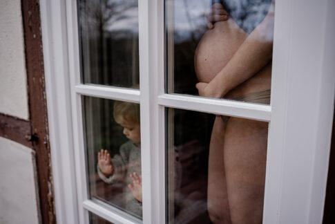 Mutter mit Babybauch und Kleinkind am Fenster