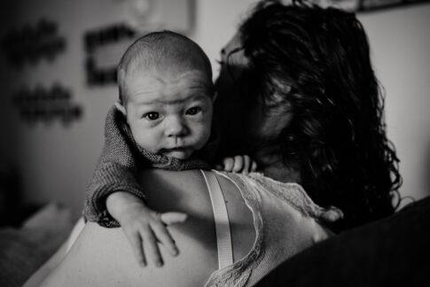 Neugeborenes schaut über die Schulter der Mama