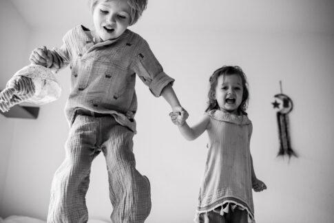 Kinder springen auf Bett