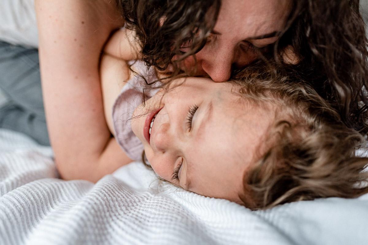 Mama gibt Tochter einen Pupskuss auf den Hals bei Toberei beim Wochenbettshooting in Gifhorn