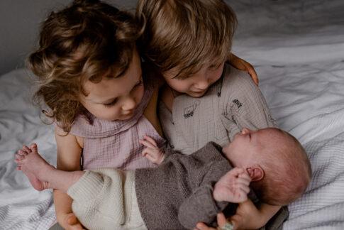 geschwisterkinder bestaunen Neugeborenes