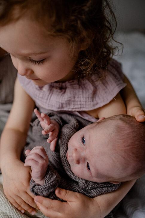 Schwester hält Neugeborenes auf dem Arm