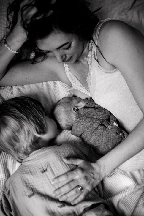 Mutter blickt stolz im Liegen auf ihre Kinder