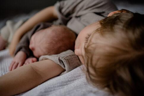 Großer Bruder liegt mit Neugeborenen auf Bett