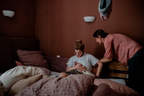 Doula Wiebke Niemann hilft der Mama sich im Bett hizusetzen