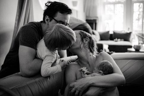 Mutter gibt großen Bruder nach Geburt einen Kuss. Sie sitzt noch im Geburtspool mit Baby auf dem Arm. Geburtsfotografie Celle