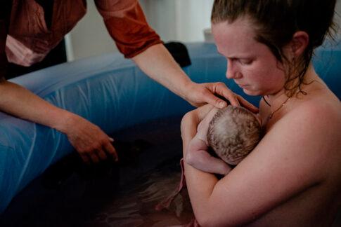 Mutter sitzt im Geburtspool nach Geburt