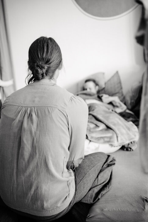 Doula Wiebke Niemann wartet neben der frischgebackenen Mutter